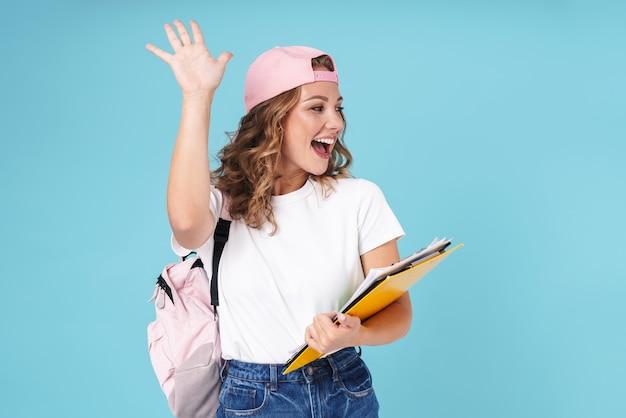 Wesoła urocza dziewczyna uczennica niosąca plecak i trzymająca podręczniki, stojąc na białym tle na niebiesko, machając ręką
