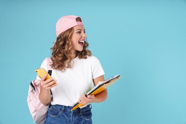 Wesoła, urocza dziewczyna uczennica niosąca plecak i trzymająca podręczniki, stojąc na białym tle na niebiesko, używając telefonu komórkowego