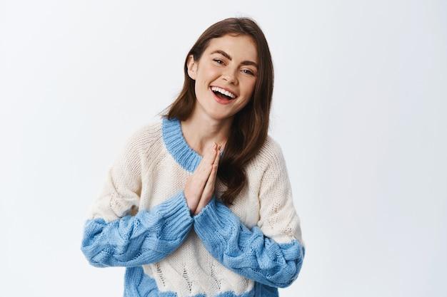 Wesoła urocza kobieta mówi dziękuję, trzymając ręce splecione w modlitwie i uśmiechając się z wdzięcznością, ubrana w sweter, wyrażająca uznanie i wdzięczność, biała ściana