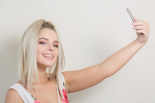 Wesoła urocza kobieta robi autoportret na smartfonie na szarym tle