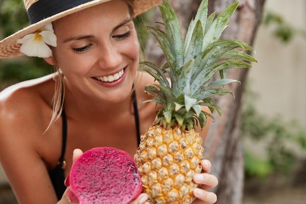 Wesoła, urocza kobieta w słomkowym kapeluszu cieszy się wakacjami na tropikalnej plaży, trzyma egzotyczny ananas i owoc smoka