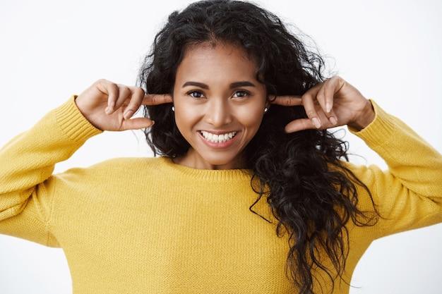 Wesoła urocza kobieta w żółtym swetrze czekająca na świąteczny huk fajerwerków, zatrzaśnięta palcami uszy w oczekiwaniu na głośny hałas, uśmiechnięta szeroko, entuzjastyczna i optymistyczna