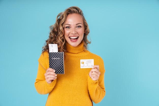 Wesoła urocza młoda dziewczyna nosi sweter stojący na białym tle na niebiesko, pokazując paszport i bilety lotnicze oraz kartę kredytową