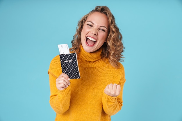 Wesoła urocza młoda dziewczyna nosi sweter stojący na białym tle na niebiesko, pokazując paszport i bilety lotnicze