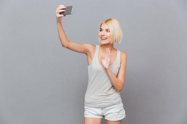 Wesoła urocza młoda kobieta robi selfie za pomocą telefonu komórkowego nad szarą ścianą