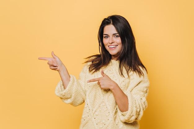 Wesoła urocza młoda kobieta z szerokim uśmiechem, wskazuje dwoma palcami przednimi w pustej przestrzeni, nosi żółty sweter, izolowany nad żółtą ścianą. kup tę rzecz ze zniżką lub wyprzedażą