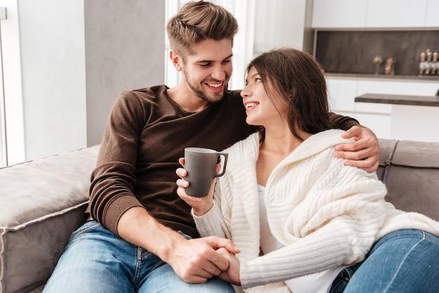 Wesoła urocza młoda para siedzi i pije kawę na kanapie w domu