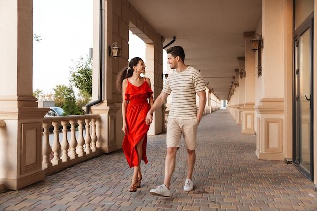 Wesoła urocza para trzymająca się za ręce i uśmiechnięta podczas spaceru w pobliżu pięknego budynku