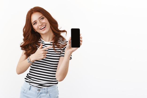 Wesoła urocza rudowłosa dziewczyna chwali się swoim nowym telefonem, trzyma smartfon wskazujący mobilny wyświetlacz, uśmiecha się radośnie, poleca korzystanie z aplikacji, pokazuje swój profil w mediach społecznościowych, biała ściana