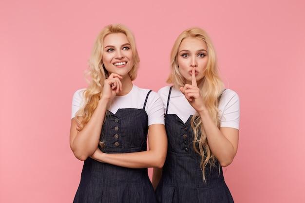 Wesoła, urocza siwowłosa dama z luźnymi włosami trzymająca brodę z uniesioną ręką i uśmiechnięta radośnie, podczas gdy jej poważna blond siostra podnosi rękę z gestem wyciszenia do ust