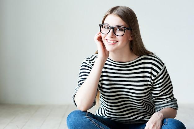 Wesoła uroda. piękna młoda kobieta w pasiastym ubraniu siedzi na drewnianej podłodze i trzyma rękę na brodzie