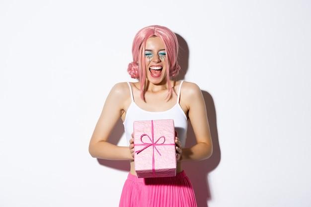 Wesoła urodzinowa dziewczyna wygląda na podekscytowaną ubraną w różową perukę krzyczącą z radości otrzymującą prezent urodzinowy na stojąco...
