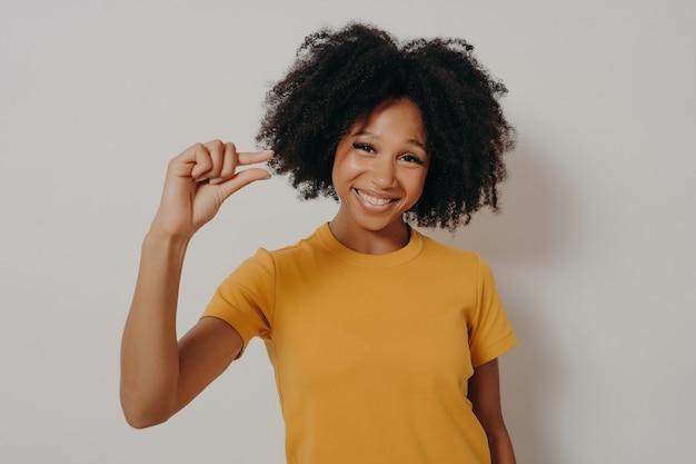Wesoła uśmiechnięta afroamerykanka gestykuluje palcami mały rozmiar, prosi o trochę czasu lub mierzy za mały przedmiot, pokazuje coś minimalistycznego, ubrana swobodnie stoi w tle studia