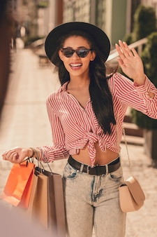 Wesoła uśmiechnięta dama z torbami na zakupy macha ręką na ulicy