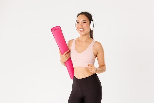Wesoła, uśmiechnięta dziewczyna fitness azjatyckich w słuchawkach i odzieży sportowej idąca na siłownię z gumową matą, pospiesz się na zajęcia jogi podekscytowana, białe tło.