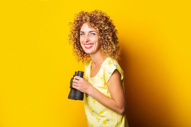 Wesoła, uśmiechnięta dziewczyna kręcone, trzymając w rękach lornetkę na żółtej powierzchni