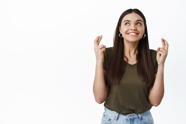 Wesoła uśmiechnięta dziewczyna mająca nadzieję, trzymające kciuki na szczęście, życząca sobie czegoś, chce czegoś i marzy o tym, stojąc przy białej ścianie