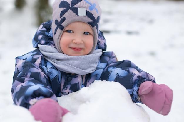 Wesoła, uśmiechnięta dziewczyna malucha na sobie zimowe ubrania, zabawy na zewnątrz na podwórku wiejskiego domu. pogoda jest śnieżna