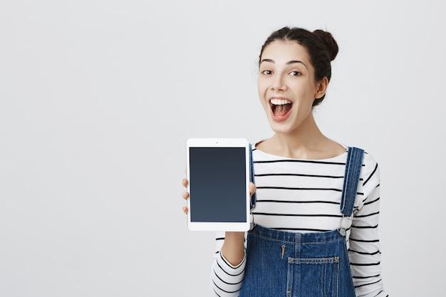 Wesoła uśmiechnięta kobieta promuje aplikację na cyfrowy tablet, pokazuje ekran