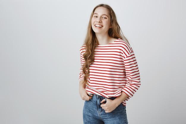 Wesoła uśmiechnięta nastolatka stojąca szczęśliwa na szarej ścianie