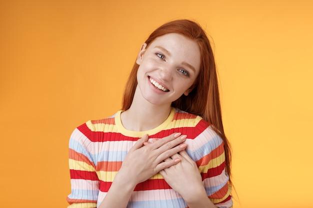 Wesoła wdzięczna namiętna stylowa ruda europejska dziewczyna dziękuję najdroższy przyjaciel piękny słodki prezent prasa dłonie serduszko uśmiechnięta szeroko odchylana głowa rozbawiona z wdzięcznością doceniam, pomarańczowe tło.