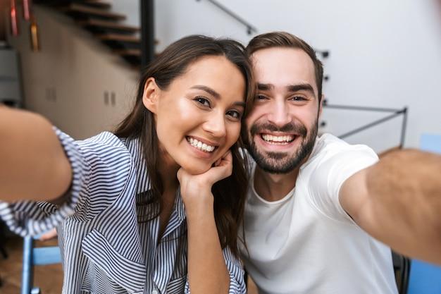 Wesoła, wieloetniczna para, biorąc selfie, siedząc w kuchni
