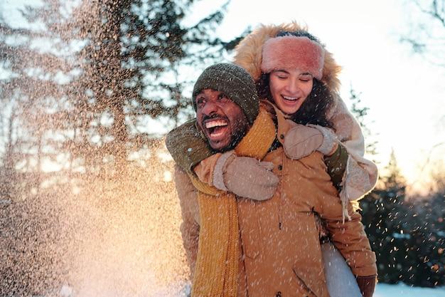 Wesoła, wielorasowa para w zimowych strojach, śmiejąca się, gdy dziewczyna obejmuje swojego chłopaka