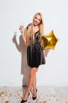 Wesoła, wspaniała młoda kobieta trzyma balon w kształcie gwiazdy i pije szampana na białym tle
