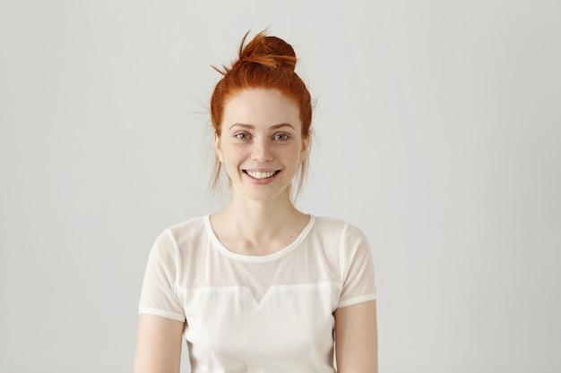 Wesoła, wspaniała młoda kobieta ubrana w rude włosy w węzeł uśmiecha się radośnie, otrzymując pozytywne wiadomości. ładna dziewczyna ubrana w białą bluzkę patrząc z podekscytowanym radosnym uśmiechem