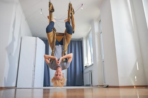 Wesoła, wysportowana blondynka joginka ze splecionymi rękami wykonująca ćwiczenie inwersji na hamaku