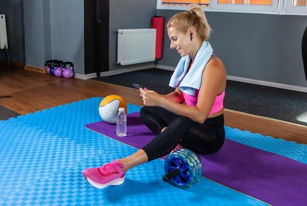 Wesoła wysportowana kobieta siedzi na macie, odpoczywa po treningu z ręcznikiem na szyi i korzysta ze smartfona