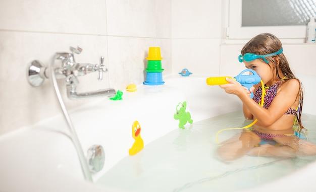 Wesoła, zabawna dziewczyna w niebieskich szklankach do wody bawi się pistoletem na wodę, siedząc w łazience z wodą i jasnymi zabawkami