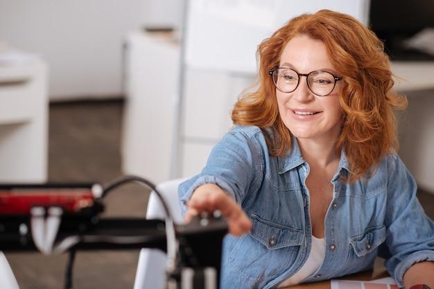 Wesoła zachwycona miła kobieta patrzy na drukarkę 3d i uśmiecha się podczas pracy z nią