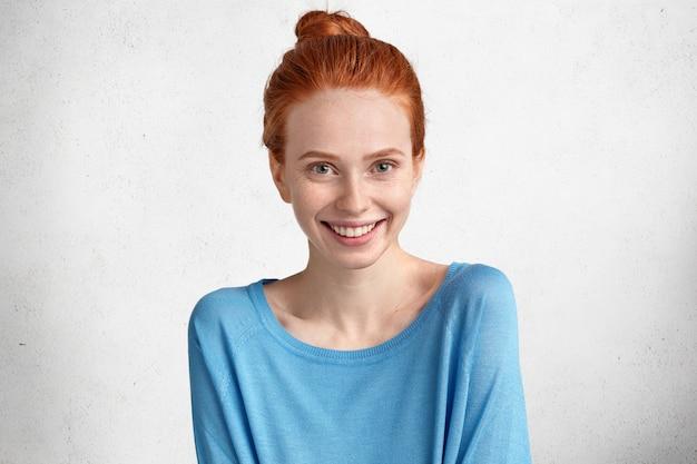 Wesoła zachwycona suczka o rudych włosach związanych w supeł, ubrana w swobodny niebieski sweter, wyraża pozytywne emocje, lubi być fotografowana