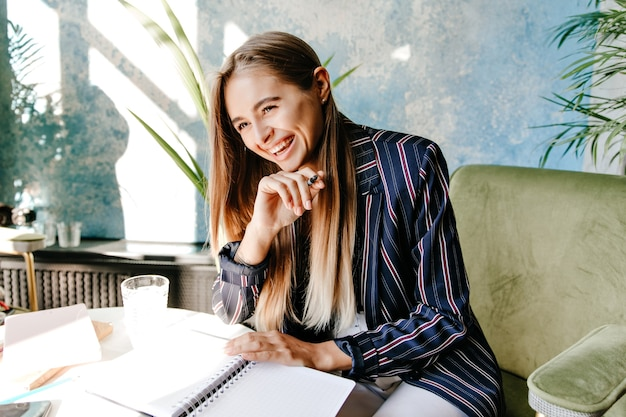 Wesoła zapracowana pani śmiejąca się w kawiarni podczas pracy. niesamowita piękna dziewczyna przygotowuje dokumenty z uśmiechem.