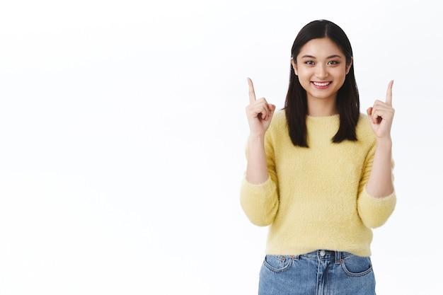 Wesoła, zdrowa i urocza azjatycka dziewczyna z błyszczącą czystą skórą, wskazując palcami w górę, aby pokazać reklamę, uśmiechnięta promująca dobry produkt, doradzająca, jaki makijaż kupić, stojąca biała ściana
