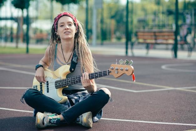 Wesoła, zrelaksowana młoda dama, uśmiechnięta i szczęśliwa, siedząc na boisku sportowym i grając na gitarze