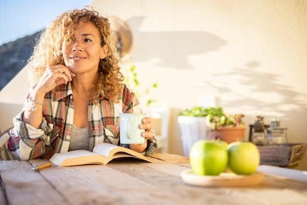 Wesoła zrelaksowana piękna kręcone blond kaukaska kobieta cieszyć się słonecznym dniem w domu na tarasie czytając książkę i pijąc herbatę lub kawę z kubka