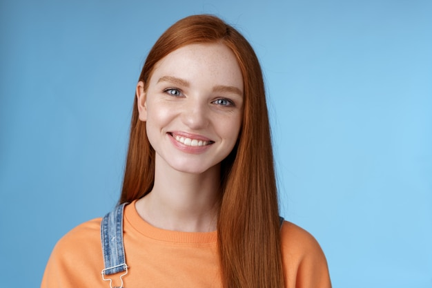 Wesoła, żywa ruda kaukaska dziewczyna uśmiecha się radośnie patrzeć na aparat miły szczery przyjacielski rozmowa ma idealne letnie wakacje rozmawiający przyjaciele stojący na niebieskim tle radosny