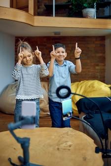 Wesołe blogerki dziecięce tańczą przed kamerą, mali vlogerki. blogowanie dzieci w domowym studio, media społecznościowe dla młodych odbiorców, transmisja internetowa w internecie