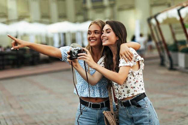 Wesołe brunetki i blond dziewczyny w kwiecistych krótkich bluzkach i dżinsowych spodniach uśmiechają się i spacerują po mieście