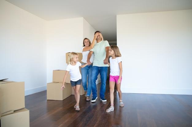 Wesołe córki i ich mama prowadzący tatę z zamkniętymi oczami w ich nowym mieszkaniu