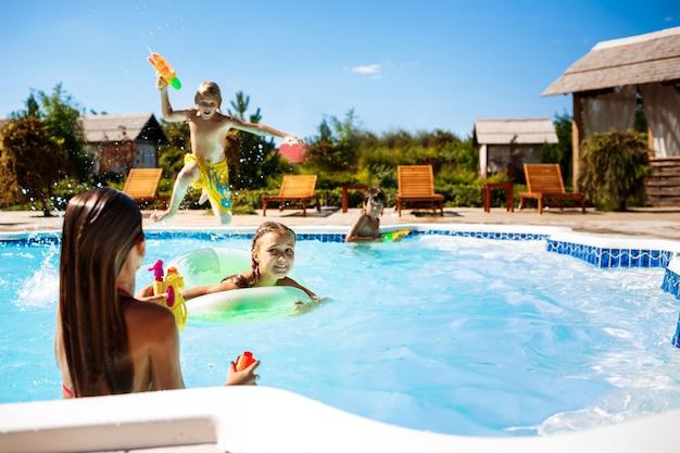 Wesołe dzieci bawiące się pistoletami wodnymi, radujące się, skaczące, pływające w basenie.