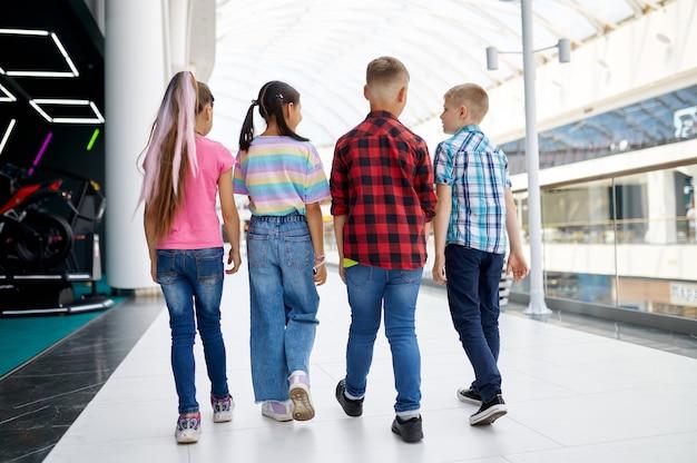 Wesołe dzieci chodzą w centrum rozrywki. chłopcy i dziewczęta bawią się, dzieciaki spędzają weekend na placu zabaw, aktywne dzieciństwo