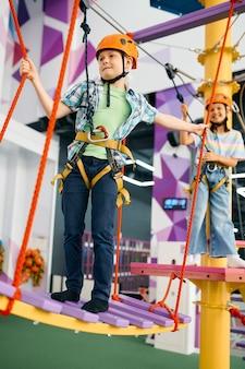 Wesołe dzieci na tyrolce w centrum rozrywki. chłopiec i dziewczynka bawią się na terenie wspinaczkowym, dzieci spędzają weekend na placu zabaw, szczęśliwe dzieciństwo