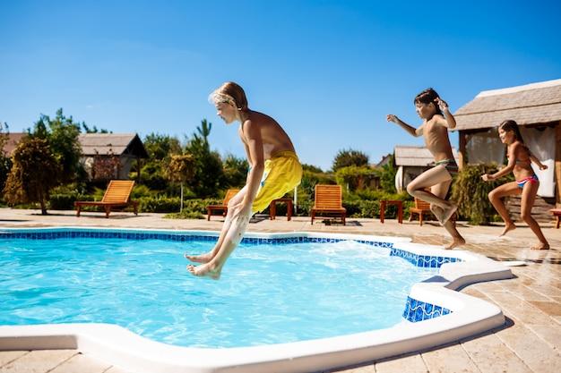 Wesołe dzieci radujące się, skaczące, pływające w basenie.