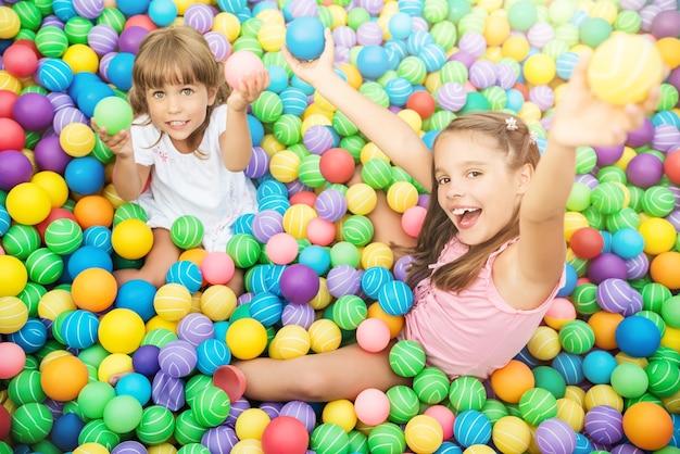 Wesołe dzieci uśmiechnięte i bawiące się w sali zabaw z plastikowymi kulkami