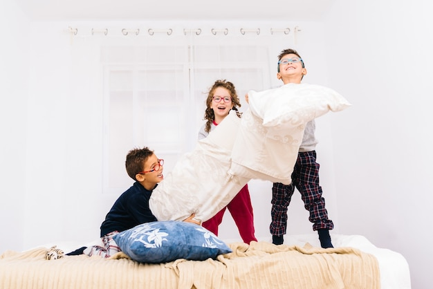 Wesołe dzieci w okularach skaczą i bawią się poduszkami na łóżku