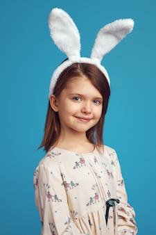 Wesołe dziecko nosi uszy królika i uśmiecha się na niebieskiej ścianie