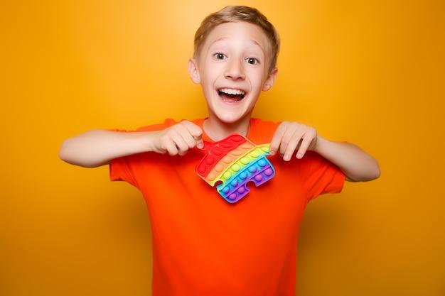Wesołe dziecko trzyma przed sobą modną antystresową silikonową zabawkę i próbuje ją rozciągnąć